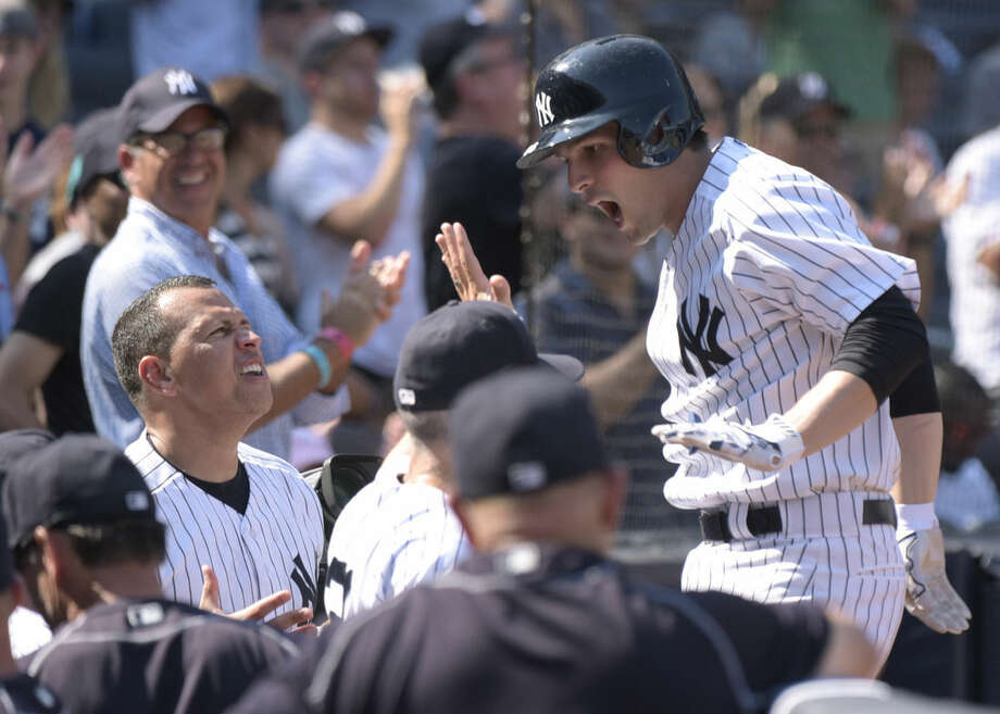 New York Yankees' John Ryan Murphy, right, celebrates with Alex Rodriguez, left, and other teammates as he comes back to the dugout after hitting a two-run home run during the fifth inning of a baseball game against the Baltimore Orioles Monday, Sept. 7, 2015, at Yankee Stadium in New York. (AP Photo/Bill Kostroun)