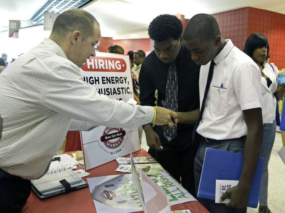FILE - In this Wednesday, June 10, 2015 file photo, Mario Polo, of Boston Market, left, talks to job seekers Herby Joseph, right, and Kingsly Jose, center, at a job fair in Sunrise, Fla. On Labor Day weekend 2015, the U.S. job market has found an old sweet spot: 5.1 percent unemployment. It's the lowest rate in more than seven years, suggestive of healthy hiring levels that have traditionally fostered rising incomes, consumer spending and economic growth. (AP Photo/Alan Diaz, File)