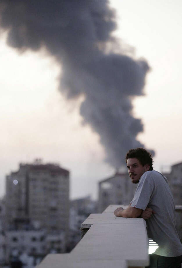 This photo taken in August, 2014 shows Associated Press video journalist Simone Camilli on a balcony overlooking smoke from Israeli Strikes in Gaza City. Camilli, 35, was killed in an ordnance explosion in the Gaza Strip, on Wednesday, Aug. 13, 2014 together with Palestinian translator Ali Shehda Abu Afash and three members of the Gaza police. Police said four other people were seriously injured, including AP photographer Hatem Moussa.(AP Photo/Lefteris Pitarakis)