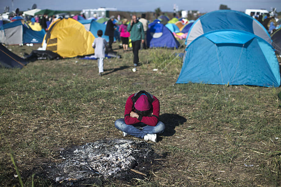 A man rests at a temporary holding camp for migrants and refugees close to Hungary's border with Serbia in Roszke, Hungary, Tuesday, Sept. 8, 2015. Hungary's prime minister Viktor Orban says he wants to speed up construction of a fence meant to stop migrants on the southern border with Serbia, a project which has missed two previous deadlines. (AP Photo/Marko Drobnjakovic)