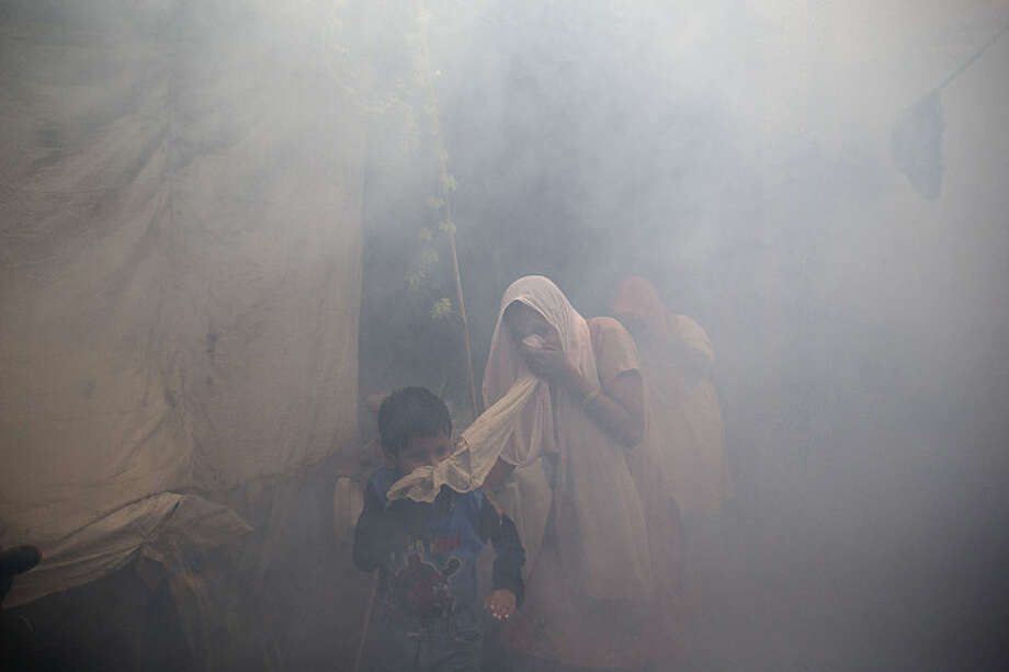 Residents cover their face and run in smoke as a municipal worker fumigates a residential area to prevent mosquitoes from breeding in New Delhi, India, Monday, Sept. 7, 2015. With several cases of Dengue fever, a mosquito-borne disease, being reported across the capital, the civic authorities are taking precautions to contain the disease. (AP Photo/Tsering Topgyal)