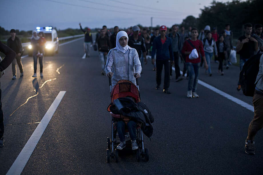 A woman pushes a stroller as she walks on the highway close to Roszke, Hungary, Monday, Sept. 7, 2015. Several hundred Arabs, Asians and Africans tired of waiting for buses broke through Hungarian police lines near the Serbian border Monday and marched north on the main highway towards Budapest as authorities once again demonstrated an inability to control the human tide passing through Hungary. (AP Photo/Marko Drobnjakovic)