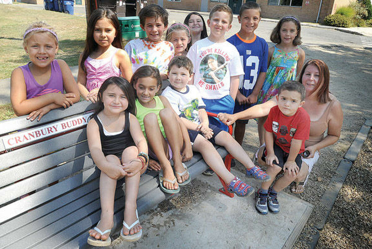 """Norwalk middle school parent Lori Keegan on the right, with Cranbury school children has created a """"buddy bench""""at Cranbury Elementary to raise awareness for suicide prevention. Hour photo/Matthew Vinci"""