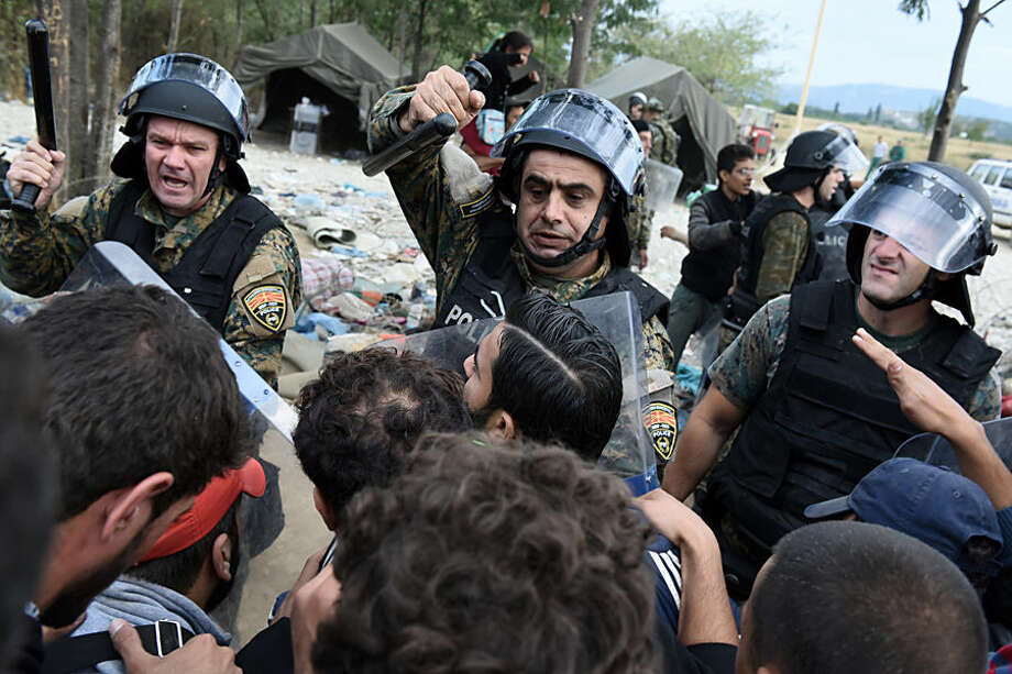 Macedonian policemen scuffle with refugees and migrants as they wait to pass the borders from the northern Greek village of Idomeni, to southern Macedonia, Monday, Sept. 7, 2015. The country has borne the brunt of a massive refugee and migration flow of people heading into the European Union. (AP Photo/Giannis Papanikos)