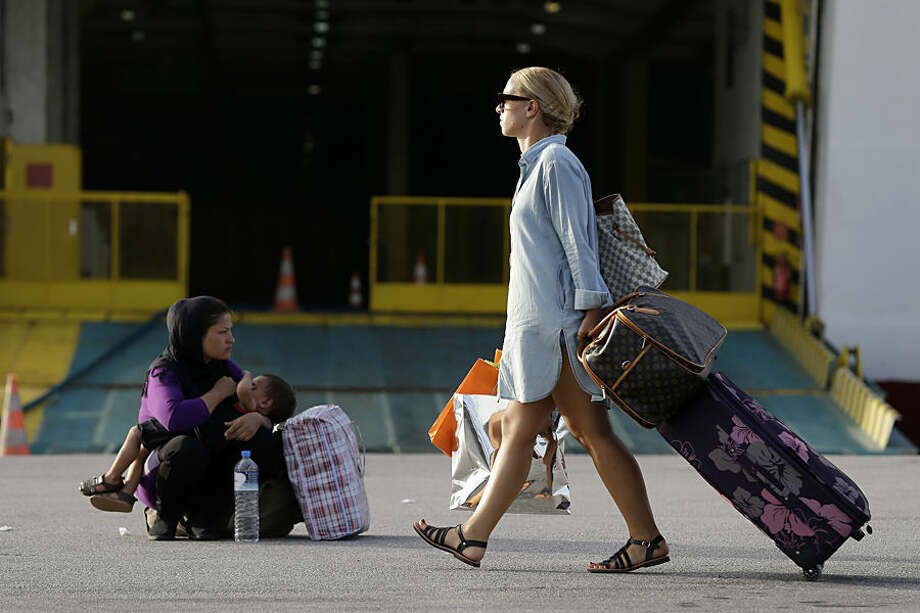 A traveler passes next to an Afghan woman who breastfeeds her baby at the Athens' port of Piraeus on Monday, Sept. 7, 2015. About 2,500 refugees and migrants arrived with the ferry Eleftherios Venizelos as Frontex, the EU border agency, says more than 340,000 asylum seekers have entered the 28-nation bloc this year, the majority fleeing war and human rights abuses in Syria, Afghanistan, Iraq, Somalia and Eritrea. (AP Photo/Thanassis Stavrakis)