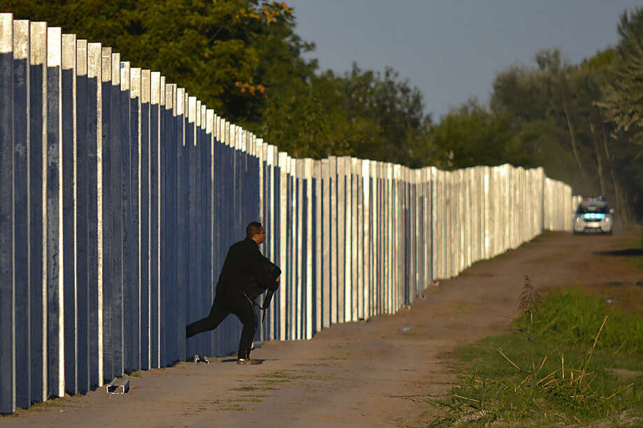 A migrant runs after he entered the territory of Hungary by crossing the temporary protection fence along the Hungarian-Serbian border as a Hungarian police car approaches at Roszke, 180 kms southeast of Budapest, Hungary, Monday, Sept. 7, 2015. (Edvard Molnar/MTI via AP)