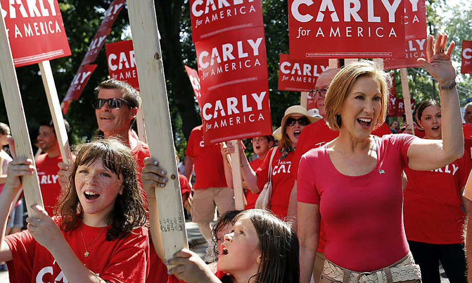 Republican presidential candidate Carly Fiorina, the former Hewlett-Packard chief executive waves as she and supporters march in the Labor Day parade Monday, Sept. 7, 2015, in Milford, N.H. (AP Photo/Jim Cole)