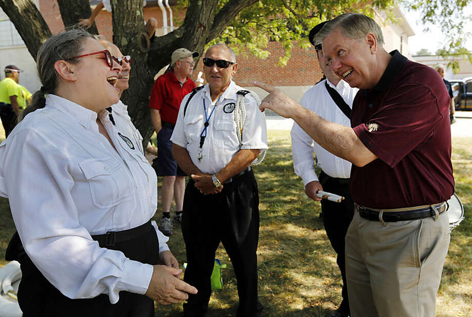 Republican presidential candidate Sen. Lindsey Graham, R-S.C., talks with band players before marching in the Labor Day parade Monday, Sept. 7, 2015, in Milford, N.H. (AP Photo/Jim Cole)