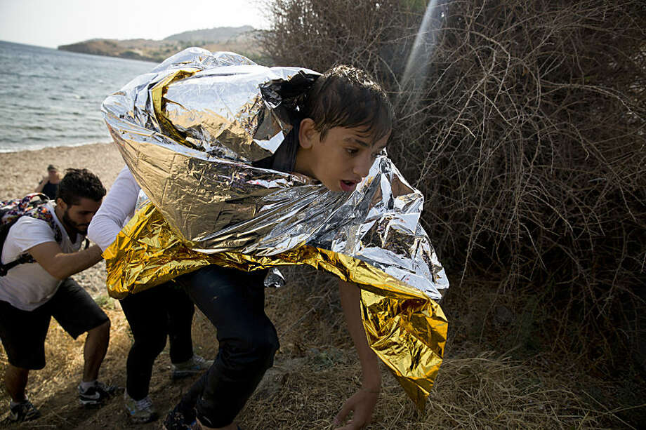 A young Syrian boy, wrapped with a thermal blanket, arrives with others after crossing aboard a dinghy from Turkey, on the island of Lesbos, Greece, Monday, Sept. 7, 2015. The island of some 100,000 residents has been transformed by the sudden new population of some 20,000 refugees and migrants, mostly from Syria, Iraq and Afghanistan. (AP Photo/Petros Giannakouris)