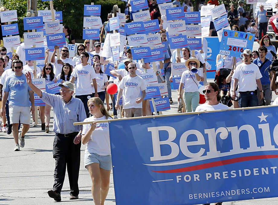 Democratic presidential candidate Sen. Bernie Sanders, I-Vt., waves as he marches with supporters in the Labor Day parade Monday, Sept. 7, 2015, in Milford, N.H. (AP Photo/Jim Cole)