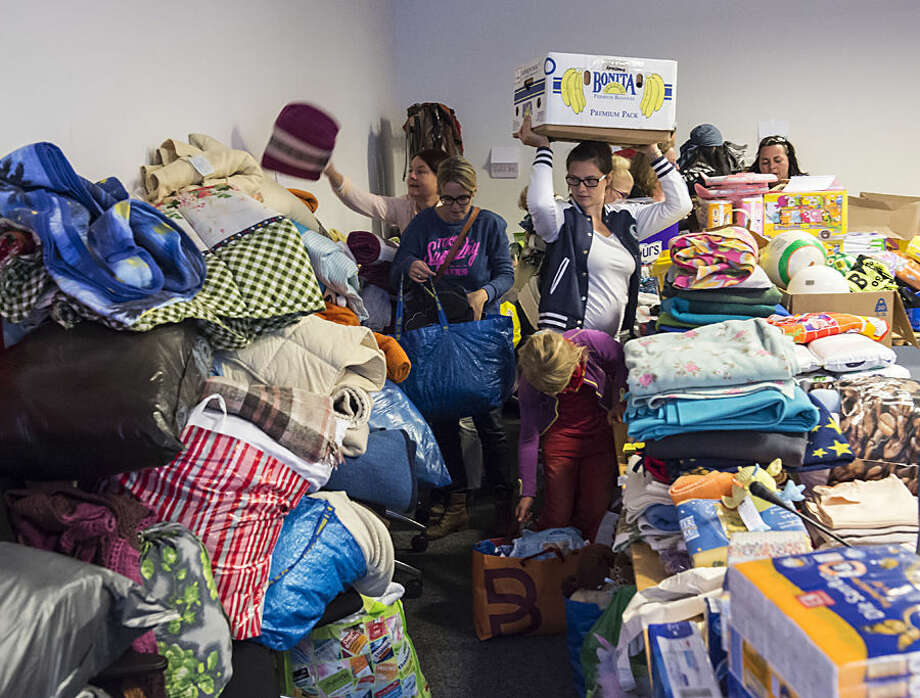 Volunteers help organize food and clothing aid as they prepare to welcome migrants, in a fraction party room in the regional parliament Thuringia in Erfurt, Germany, Monday, Sept. 7, 2015. Some hundreds of refugees are scheduled to arrive during the next hours in central Germany. (AP Photo/Jens Meyer)