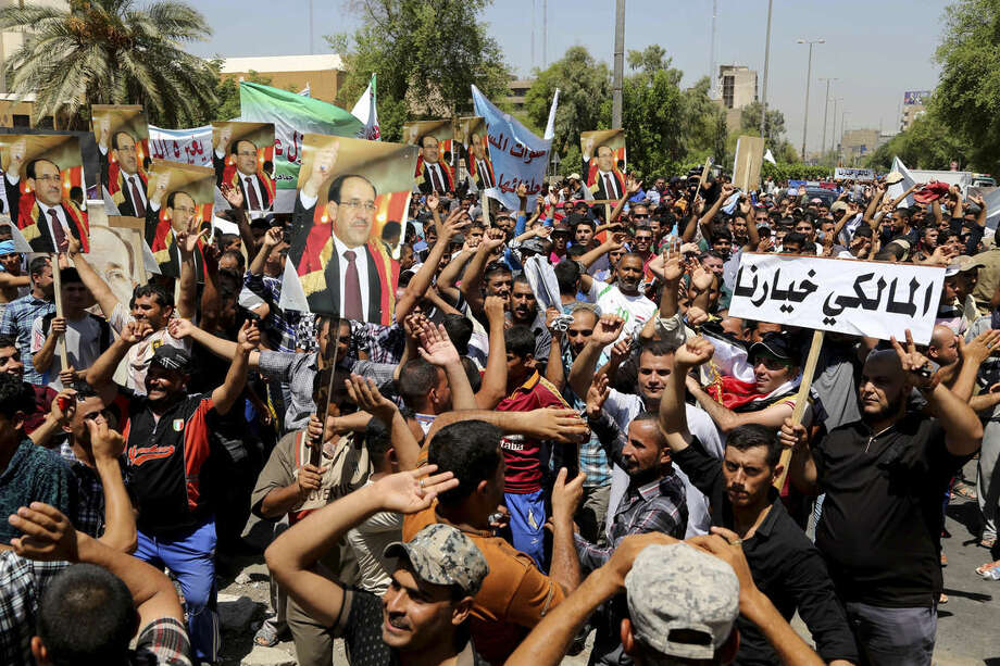 "Pro-government supporters of Prime Minister Nouri al-Maliki, chant slogans during a demonstration in Baghdad, Iraq, Wednesday, Aug 13, 2014. Tanks and Humvees were positioned on Baghdad bridges and at major intersections on Wednesday, with security personnel more visible than usual as pro-Maliki demonstrators took to Firdous Square in the capital, pledging their allegiance to him. Arabic on the placard at right reads, ""al-Maliki is our choice."" (AP Photo/Karim Kadim)"