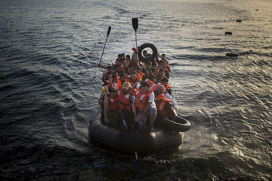 """Refugees and migrants who crossed from Turkey aboard a dinghy approach the coast of the northeastern Greek island of Lesbos, Monday, Sept. 7, 2015. Greece's caretaker government, appointed ahead of elections Sept. 20, says at least two-thirds of the estimated 15,000-18,000 refugees and economic migrants stranded in """"miserable"""" conditions on the Aegean island will be ferried to the mainland in the next five days. (AP Photo/Santi Palacios)"""