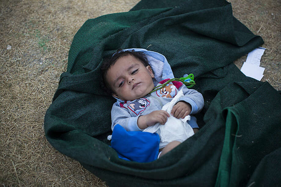A baby lays on the ground as his mother waits for the registration and the issuing of travel documents of her family at a soccer stadium in Mytilene, on the northeastern Greek island of Lesbos, Tuesday, Sept. 8, 2015. More than 15,000 refugees and migrants are stranded on the Aegean island, awaiting screening before they can board a ferry to the Greek mainland from where they head north through Macedonia, Serbia and Hungary to seek asylum in more prosperous European countries. (AP Photo/Santi Palacios)