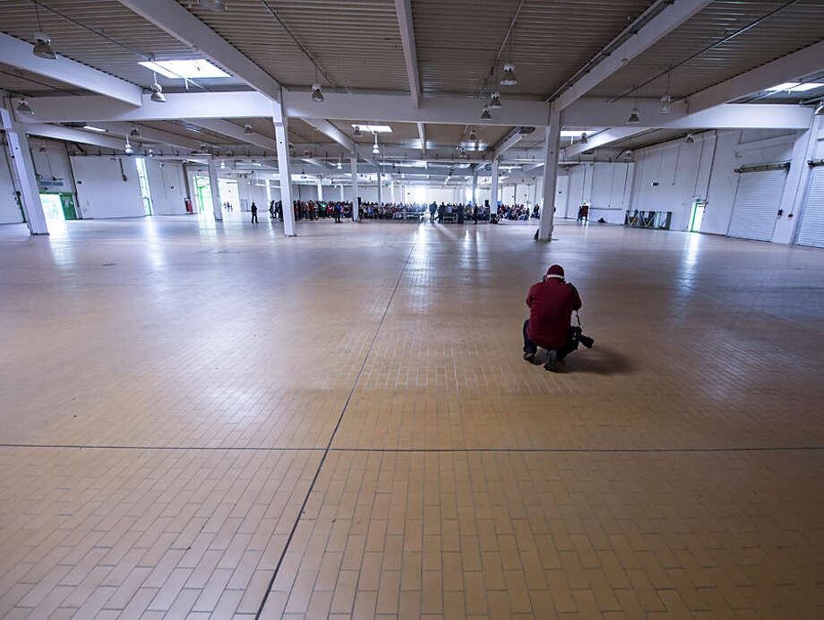 Some hundreds of residents stand together, inside a former marketplace for construction materials, during a information meeting of the city's major in Erfurt, Germany, Monday, Sept. 7, 2015. The hall is one of the planned accommodation sites for migrants, as hundreds of migrants are scheduled to arrive during the next hours in central Germany. (AP Photo/Jens Meyer)