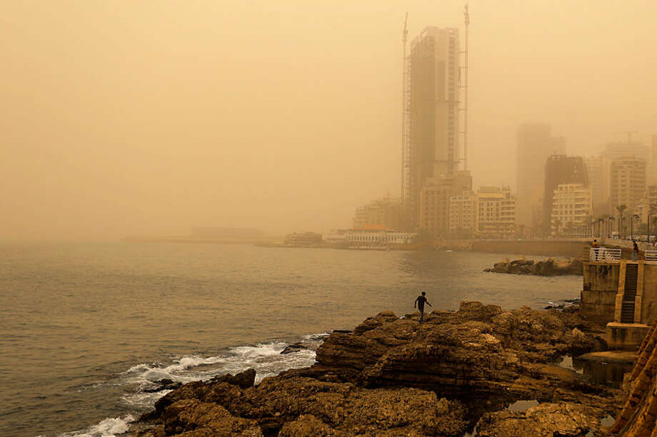 A man walks on the rocky coastal area along the Beirut coastline during a sandstorm in Beirut, Lebanon, Tuesday, Sept. 8, 2015. An unseasonal sandstorm has hit Lebanon and Syria, reducing visibility and sending dozens to hospitals with breathing difficulties because of the fine dust. (AP Photo/Hassan Ammar)