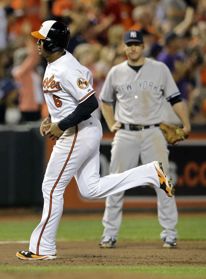 Baltimore Orioles' Jonathan Schoop, front, rounds the bases past New York Yankees third baseman Chase Headley (12) after hitting a solo home run in the eighth inning of a baseball game, Wednesday, Aug. 13, 2014, in Baltimore. Baltimore won 5-3. (AP Photo/Patrick Semansky)