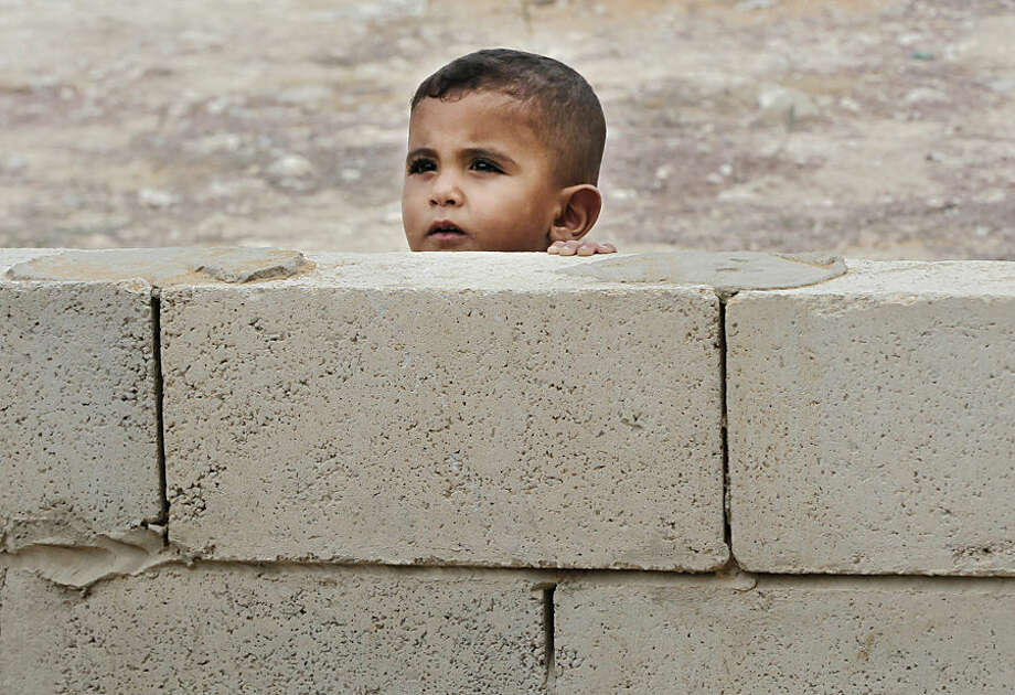 A Syrian boy peeks from behind a wall near a mobile clinic at a refugee camp in the Lebanese town of Zahrani.