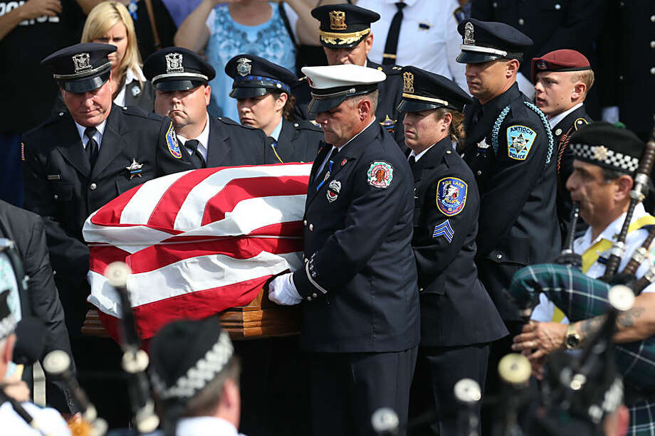 The casket of slain Fox Lake police Lt. Charles Joseph Gliniewicz is loaded into the hearse at Antioch Community High School, Monday, Sept. 7, 2015 in Antioch, Ill. Hundreds of law enforcement officers are attending the funeral of the suburban Chicago police officer who was fatally shot last week. (Stacey Wescott/Chicago Tribune via AP)