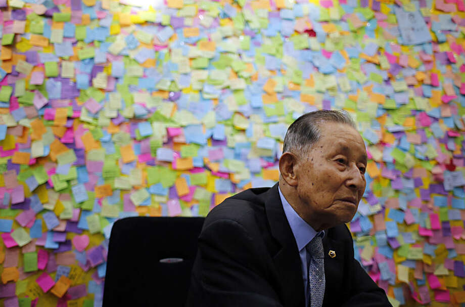 South Korean Jun Joo-eul, 85, who was separated from his family during the Korean War, sits in front of messages wishing for the family reunions between two Koreas at the video meeting room for separated families at the Korea Red Cross headquarters in Seoul, South Korea, Tuesday, Sept. 8, 2015. North and South Korea agreed Tuesday to hold reunions next month of families separated by the Korean War in the early 1950s, a small but important bit of progress for rivals that just last month were threatening each other with war. (AP Photo/Lee Jin-man)