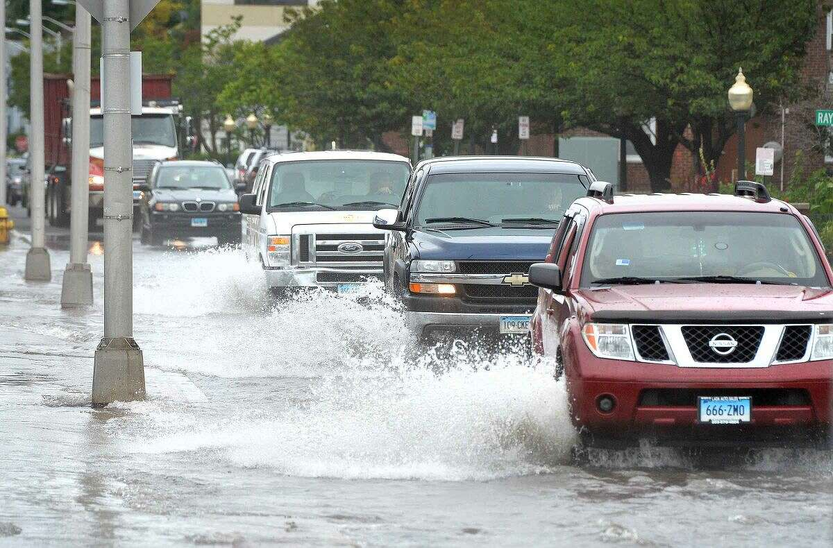 Hour Photo/Alex von Kleydorff Water Street in SoNo was difficult to navigate as heavy rains and the high tide caused flooding on Wednesday afternoon