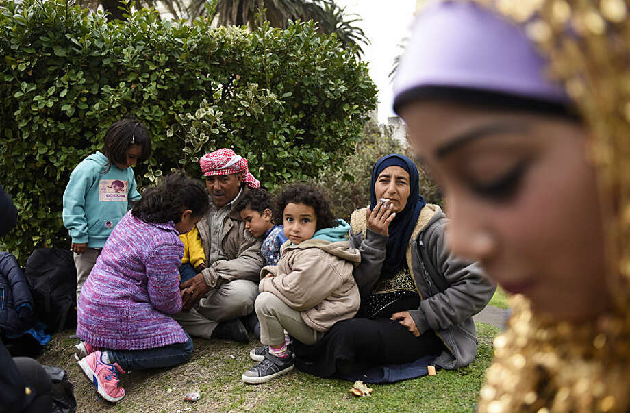 Syrian refugees gather outside the government house at Independence Square, in Montevideo, Uruguay, Monday, Sept. 7, 2015. Some members of a group of Syrian refugees who were welcomed to Uruguay last year are staging a protest outside the government house, demanding authorities allow them to leave the South American country. They say local officials promised more than they could deliver and that Uruguay is expensive and there are no jobs. (AP Photo/Matilde Campodonico)