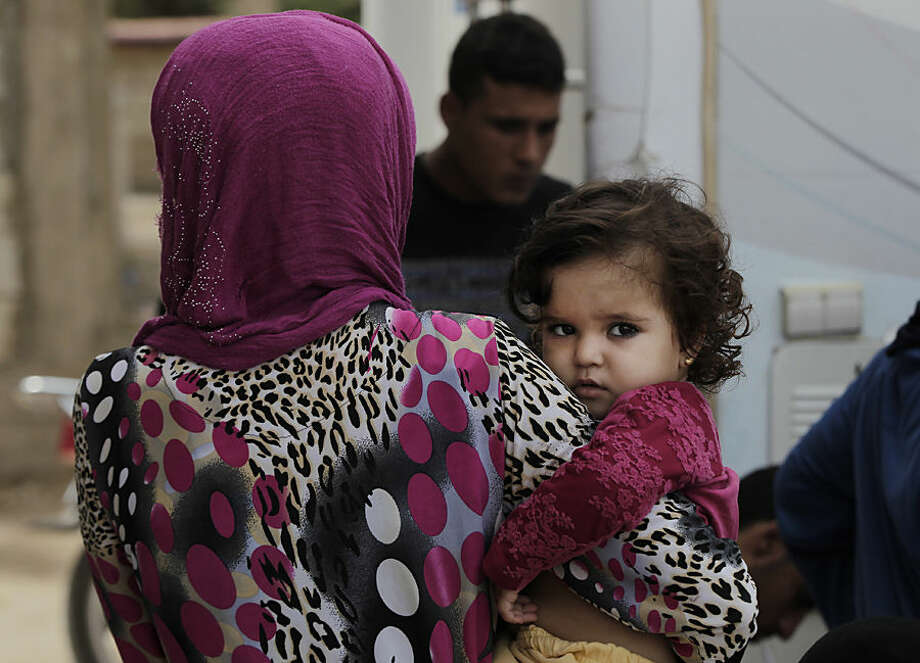 A Syrian woman waits in front of a mobile clinic as she hold her daughter at a refugee camp in the southern town of Zahrani, south of the port city of Sidon, Lebanon, Monday, Sept. 7, 2015. There are some 1.2 million registered Syrian refugees in Lebanon, many of them living in flimsy tents scattered across the country. (AP Photo/Bilal Hussein)