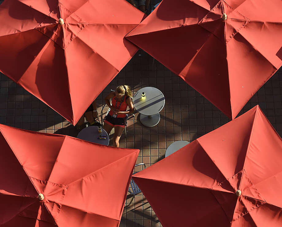 A woman sits under umbrellas on the grounds of the USTA Billie Jean King National Tennis Center during the fourth round of the U.S. Open tennis tournament, Monday, Sept. 7, 2015, in New York. (AP Photo/Kathy Kmonicek)