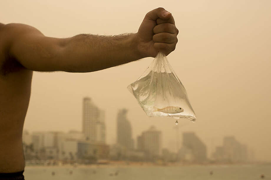 An Israeli man holds up the fish he caught on the Mediterranean Sea beach front, covered with a blanket of yellow dust, in Tel Aviv, Israel, Tuesday, Sept. 8, 2015. An unseasonal sandstorm has hit the Middle East, reducing visibility and sending dozens to hospitals with breathing difficulties. (AP Photo/Oded Balilty)