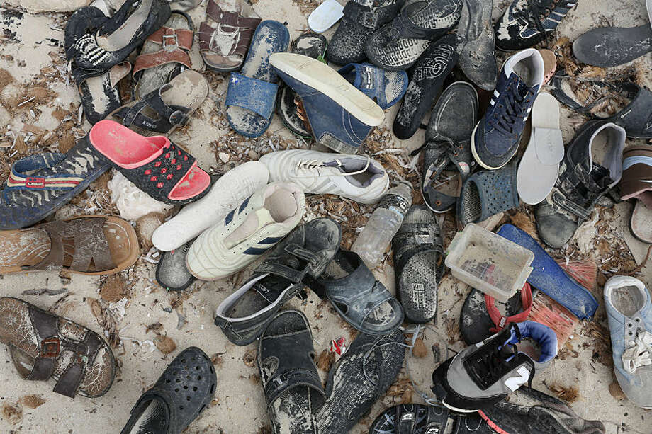 In this Monday, Sept. 7, 2015 photo, discarded shoes are piled near a smugglers' shack on the beach west of the town of Zuwara, Libya, where bodies continue to wash ashore after two fishing boats bound for Europe carrying migrants and refugees capsized off the Libyan coast on Thursday, Aug. 27, 2015. As of September 2015, more than 2,800 migrants have died trying to reach Europe, mostly at sea, according to the International Organization for Migration. (AP Photo/Mohamed Ben Khalifa)