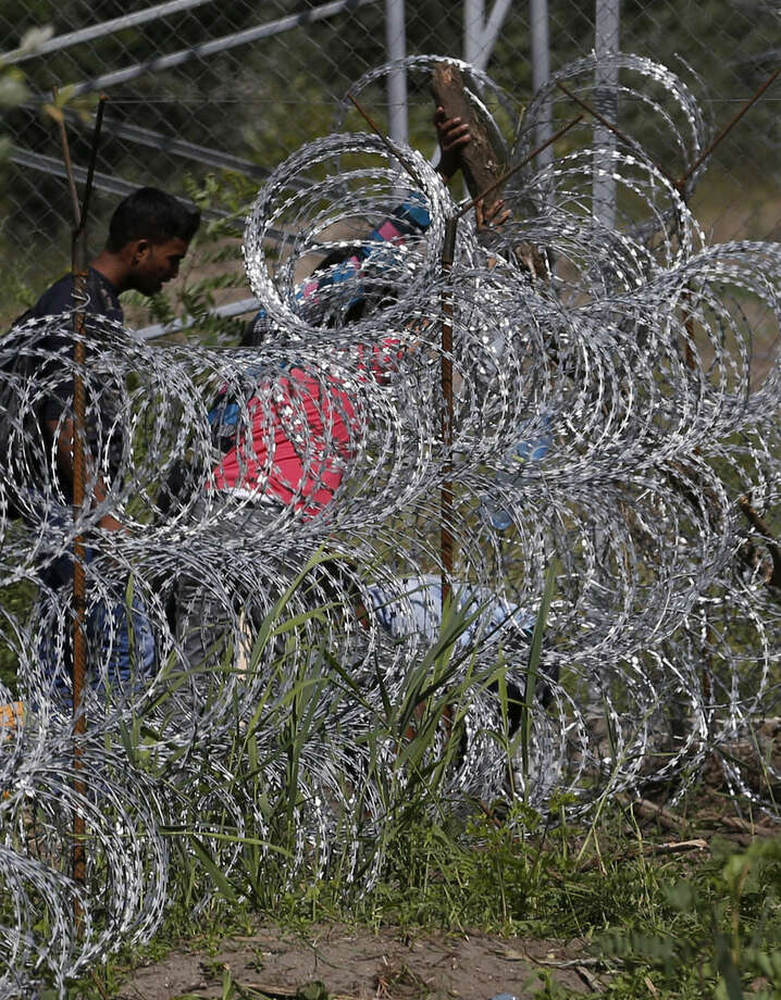 People try to cross under a wire fence on the Serbian border with Hungary, near the village of Hajdukovo, Serbia, Monday, Sept. 7, 2015. Hungarian police stood by as thousands of migrants hopped cross-border trains Sunday into Austria, taking advantage of Hungary's surprise decision to stop screening international train travelers for travel visas, a get-tough measure that the country had launched only days before to block their path to asylum in Western Europe. (AP Photo/Darko Vojinovic)