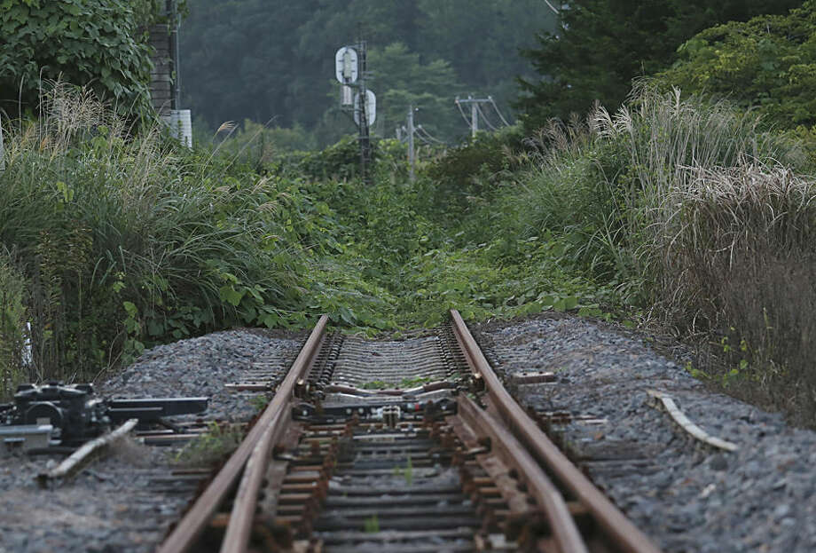In this Friday, Sept. 4, 2015 photo, the rusty train track of Joban line is covered with weeds near the Tatsuta Station in Naraha town, Fukushima prefecture, northeastern Japan. This past weekend, Naraha became the first of seven towns that had been entirely evacuated to reopen since the March 11, 2011, disaster, when a tsunami slammed into the Fukushima Dai-ichi nuclear power plant, causing meltdowns and a massive radiation leak. The town's viability is far from certain, and its fate will be watched closely by authorities and neighboring towns to see if recovery is indeed possible in this radiation-contaminated land. (AP Photo/Koji Sasahara)