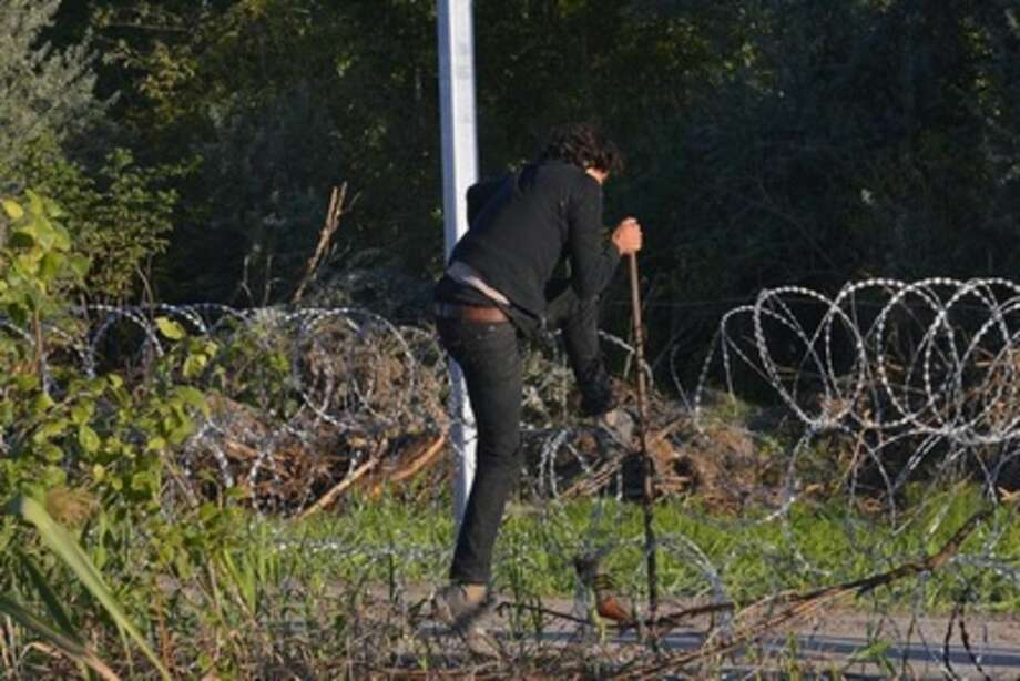 A migrant enters the territory of Hungary by crossing the temporary protection fence along the Hungarian-Serbian border at Roszke, 180 kms southeast of Budapest, Hungary, Monday, Sept. 7, 2015. (Edvard Molnar/MTI via AP)