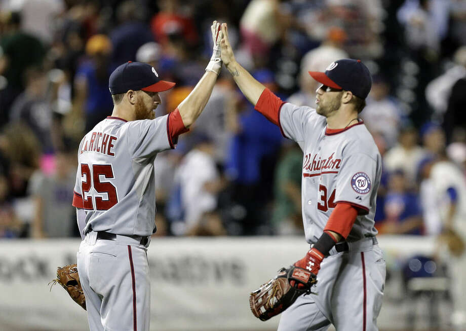 Washington Nationals' Bryce Harper (34) and Adam LaRoche (25) celebrate after a baseball game against the New York Mets Thursday, Aug. 14, 2014, in New York. The Nationals won the game 4-1. (AP Photo/Frank Franklin II)