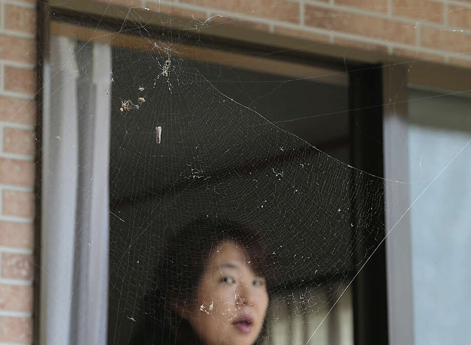 In this Friday, Sept. 4, 2015 photo, Naoko Kanai watches a spider's web at her house after returning home for the first time in about two months, in Naraha town, Fukushima prefecture, northeastern Japan. This past weekend, Naraha became the first of seven towns that had been entirely evacuated to reopen since the March 11, 2011, disaster, when a tsunami slammed into the Fukushima Dai-ichi nuclear power plant, causing meltdowns and a massive radiation leak. Kanai, a 50-year-old homemaker, is among those having trouble deciding whether to return to Naraha permanently. (AP Photo/Koji Sasahara)