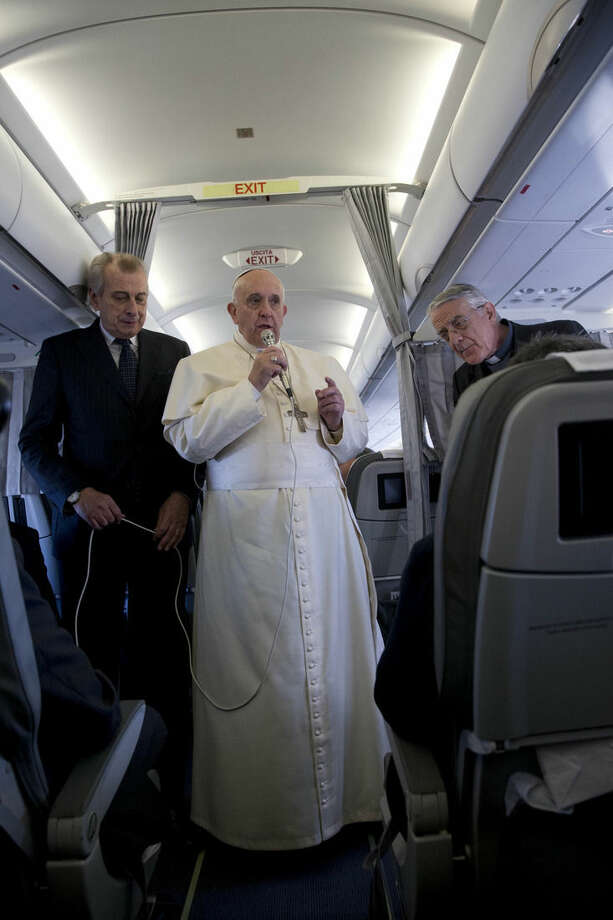 FILE - In this Tuesday, Nov. 25, 2014 file photo, Pope Francis, flanked by Vatican spokesman father Federico Lombardi, right, talks to journalists during a press conference he held aboard the papal flight on his way back from Strasbourg, eastern France, at the end of a one day visit to the European Parliament and Council. It's not just the proximity of travelling on the papal plane or tucking into the same creamy lasagna and beef filet that is clearly a Francis favorite on the Alitalia charter that ferries him around the globe. It's seeing the pope relaxed, surrounded by a handful of his closest aides, embarking on a new adventure or returning home from one, exhausted. (AP Photo/Andrew Medichini, File)