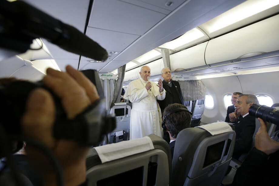 FILE - In this Tuesday, Nov. 25, 2014 file photo, Pope Francis, flanked by Vatican spokesman father Federico Lombardi, top right, talks to journalists during a press conference he held aboard the papal flight on his way back from Strasbourg, eastern France, at the end of a one day visit to the European Parliament and Council. It's not just the proximity of travelling on the papal plane or tucking into the same creamy lasagna and beef filet that is clearly a Francis favorite on the Alitalia charter that ferries him around the globe. It's seeing the pope relaxed, surrounded by a handful of his closest aides, embarking on a new adventure or returning home from one, exhausted. (AP Photo/Andrew Medichini, File)