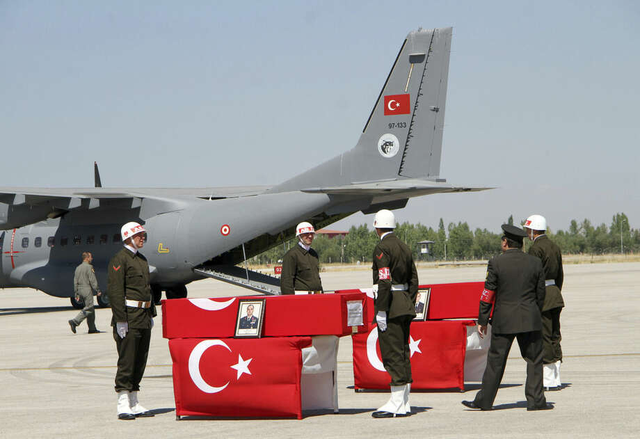 Turkish soldiers prepare the coffins of fallen comrades, including Lt. Col. Ilker Celikcan, front, before a ceremony at the military airport in Van, Turkey, Tuesday, Sept. 8, 2015, two days after 16 soldiers were killed and six others were wounded in a Kurdish rebel attack against troops in southeast Turkey on Sunday. The attack was the deadliest assault on Turkish troops since renewed fighting between the rebels and Turkey's security forces erupted in July, shattering a fragile peace process.( IHA Agency via AP ) TURKEY OUT