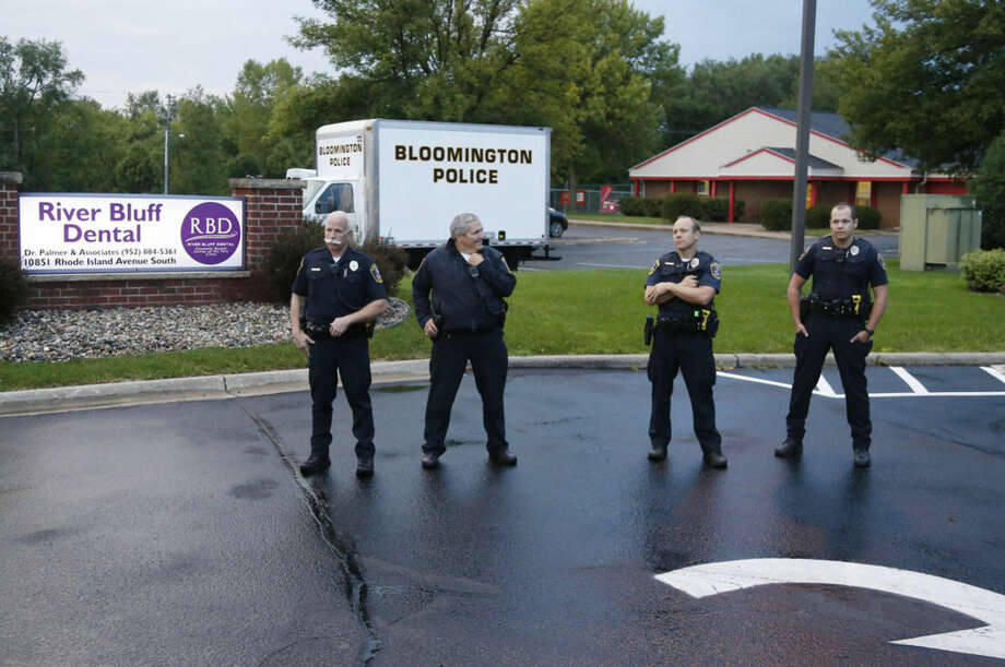 Police stand guard at the dental practice of Walter Palmer, who returned to his practice, Tuesday, Sept. 8, 2015, in Bloomington, Minn. Palmer, after weeks out of the public eye, was the subject of an international uproar after he was identified as the hunter who killed the famous lion Cecil in Zimbabwe. (AP Photo/Jim Mone)