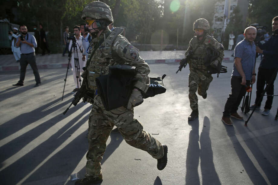 FILE - In this Saturday, Aug. 22, 2015 file photo, British soldiers run at the site of a suicide attack in the heart of Kabul, Afghanistan. Loyalists of the Islamic State group are making inroads into Afghanistan, with homegrown militants claiming fealty to IS controlling territory in some parts of the country and ruling in the same harsh fashion witnessed in Iraq and Syria, officials, military leaders and analysts said. (AP Photo/Massoud Hossaini, File)