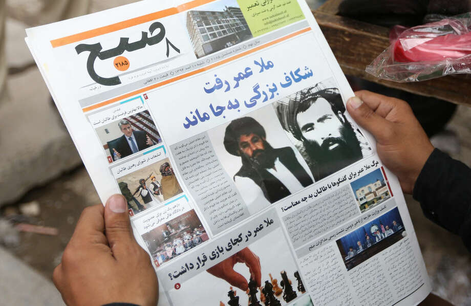 FILE - In this Saturday, Aug. 1, 2015 file photo, an Afghan man reads a local newspaper with photos of the new leader of the Afghan Taliban, Mullah Akhtar Mansoor, center, and former leader Mullah Mohammad Omar who was declared dead, in Kabul, Afghanistan. Loyalists of the Islamic State group are making inroads into Afghanistan, with homegrown militants claiming fealty to IS controlling territory in some parts of the country and ruling in the same harsh fashion witnessed in Iraq and Syria, officials, military leaders and analysts said. (AP Photo/Massoud Hossaini, File)