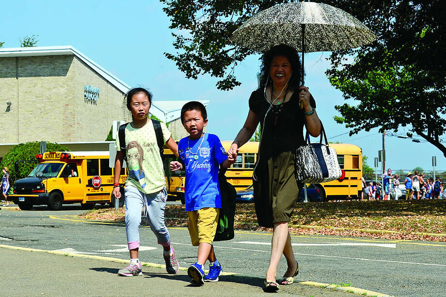 Hour photo / Erik Trautmann Meirong Zheng, right, picks up her grand children, 4th grader Emily Guo, and 2nd grader Daniel Guo, from Naramake Elementary School in Norwalk after some schools had early dismissal due to the heat and lack of air conditioning.