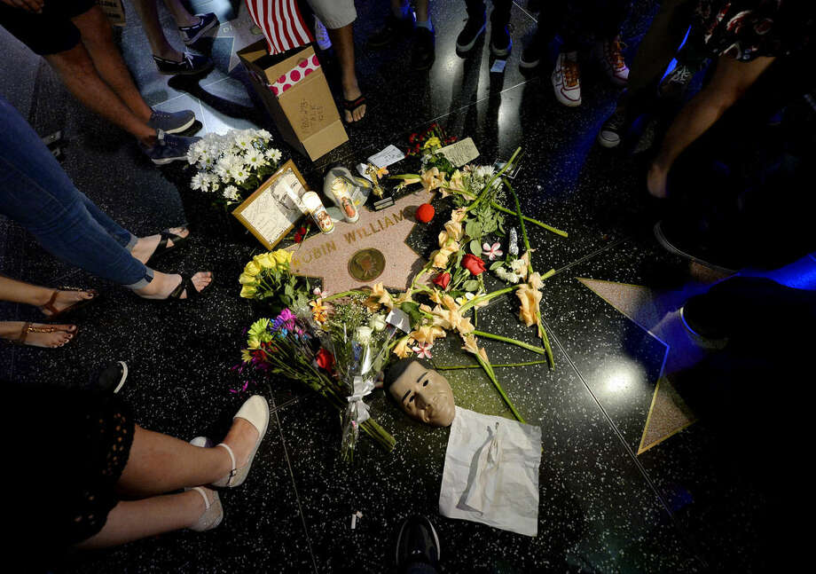 AP10ThingsToSee - Flowers are placed in memory of actor and comedian Robin Williams on his Walk of Fame star in the Hollywood district of Los Angeles, Monday, Aug. 11, 2014. Williams died Monday, he was 63. (AP Photo/Kevork Djansezian)