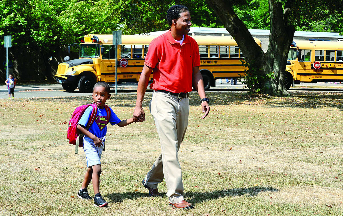Hour photo / Erik Trautmann Dondre Boyd picks up his son, kindergartner Sean Boyd, from Naramake Elementary School in Norwalk after some schools had early dismissal due to the heat and lack of air conditioning.