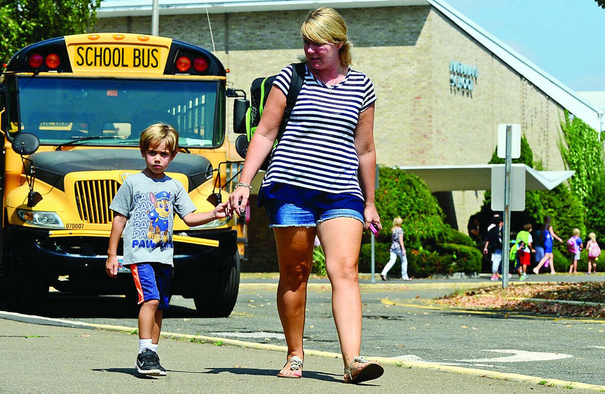 Hour photo / Erik Trautmann Niki Memoli picks up her son, kindergartner Andrew Memoli, from Naramake Elementary School in Norwalk after some schools had early dismissal due to the heat and lack of air conditioning.