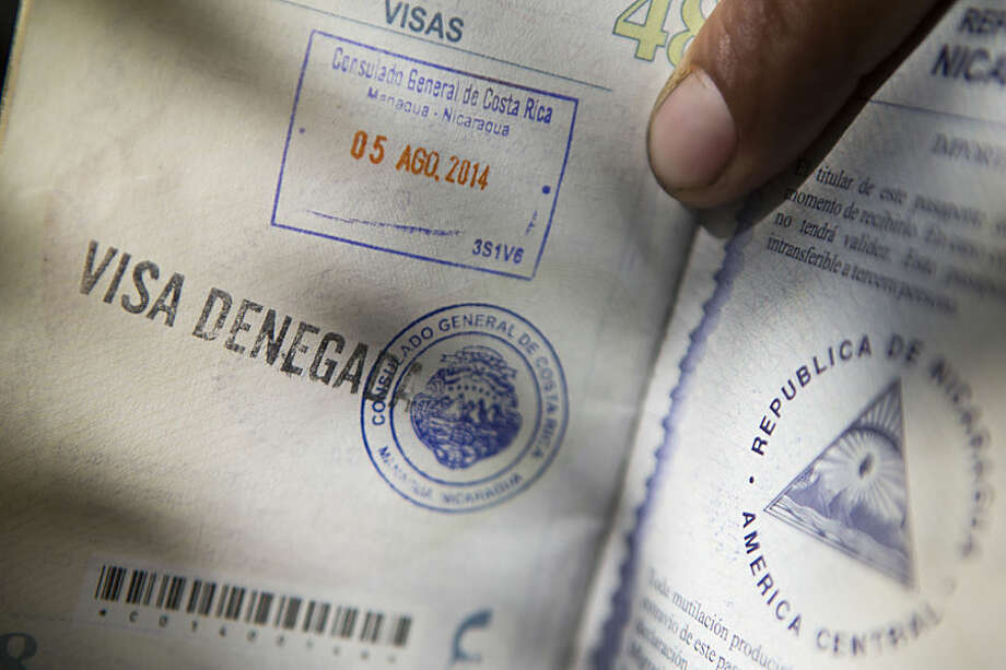 """In this Tuesday, Aug. 5, 2014 photo, a man shows his passport with a """"visa denied,"""" stamp, outside the Costa Rican consulate, where he stood in line for two days, in Managua, Nicaragua. When Nicaraguans leave, they usually stay closer to home, migrating to neighboring Costa Rica, a relatively peaceful country with a much higher standard of living than their own. (AP Photo/Esteban Felix)"""
