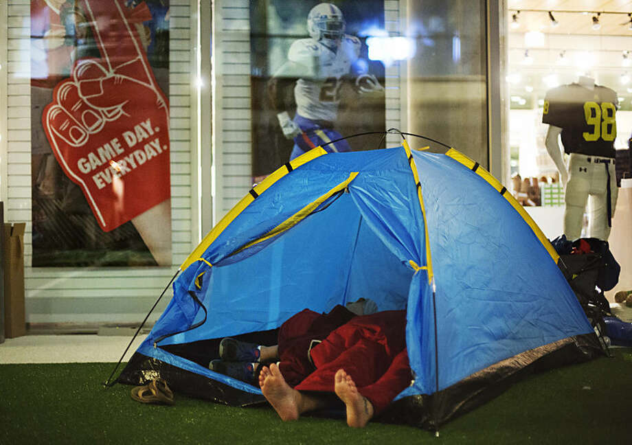 "Guests sleep in a tent next to the gift shop during a sleepover in the College Football Hall of Fame, Thursday, Aug. 14, 2014, in Atlanta. After touring the exhibits guest were served dinner on the football field before pitching their tents on the turf and settling in for the night as college football themed movies such as ""Rudy"" were played. (AP Photo/David Goldman)"