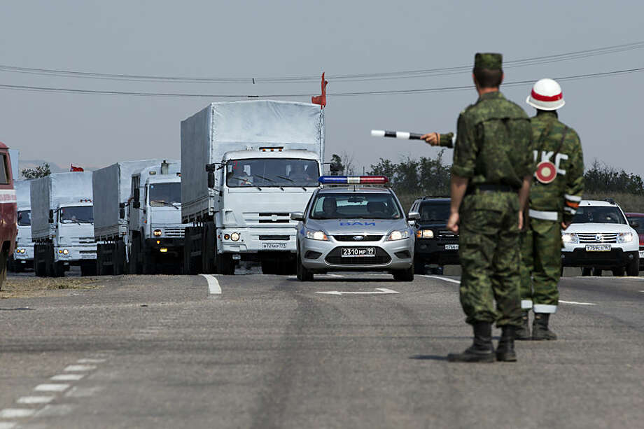 A convoy of white trucks with humanitarian aid is seen, about 28 kilometers from the the Ukrainian border, in Rostov-on-Don region, Russia, Thursday, Aug. 14, 2014. A large Russian aid convoy resumed its journey toward Ukraine Thursday, taking a road leading directly toward a border crossing controlled by pro-Russian rebels in the Luhansk region. By taking such a route, Russian appeared to be intent on not abiding by a tentative agreement to deliver aid to a government-controlled border checkpoint in the Kharkiv region, where it could more easily be inspected by Ukraine and the Red Cross. (AP Photo/Pavel Golovkin)