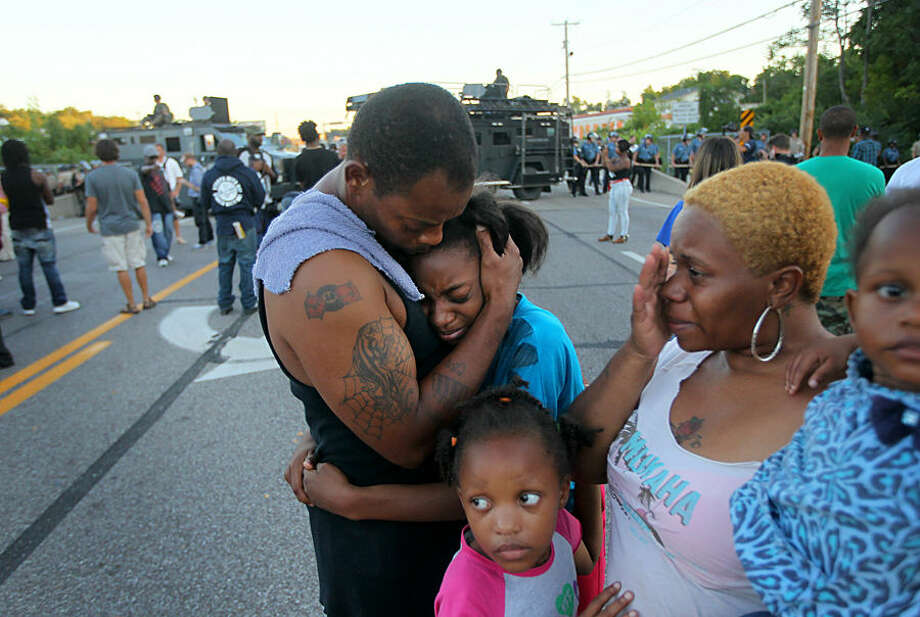 """Terrell Williams El hugs his daughter Sharell, 9, while standing with his wife, Shamika Williams, and daughters Tamika, 6, and Sharell, 2, on Wednesday, Aug. 13, 2014, in Ferguson, Mo. They were overcome with emotion after Williams El confronted police. """"I'm out here to stand for my children and their future,"""" said Williams El. (AP Photo/St. Louis Post-Dispatch, David Carson)"""