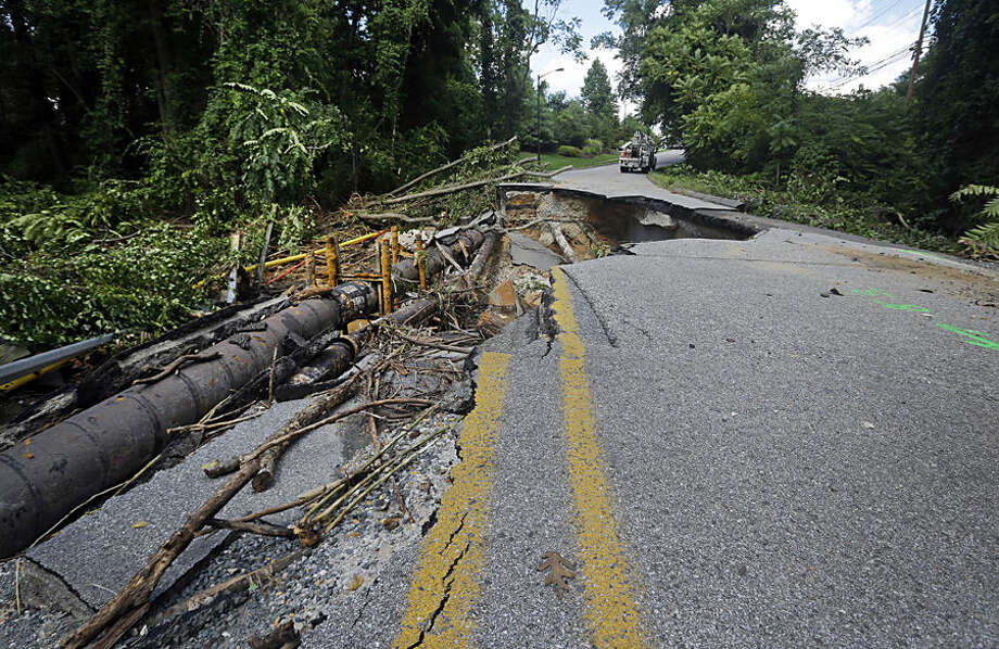 Debris sits below a damaged road, Wednesday, Aug. 13, 2014, in Glen Burnie, Md., after it was washed out by a heavy rainstorm. Tuesday's storm brought rain levels that led to flooding in low-lying areas and necessitated several water rescues around the state. (AP Photo/Patrick Semansky)